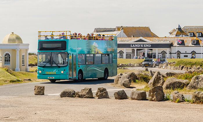An open top bus leaves Lands End